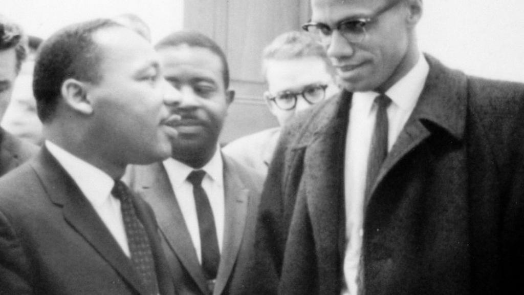Photo of Martin Luther King, Jr. and Malcolm X waiting for press conference