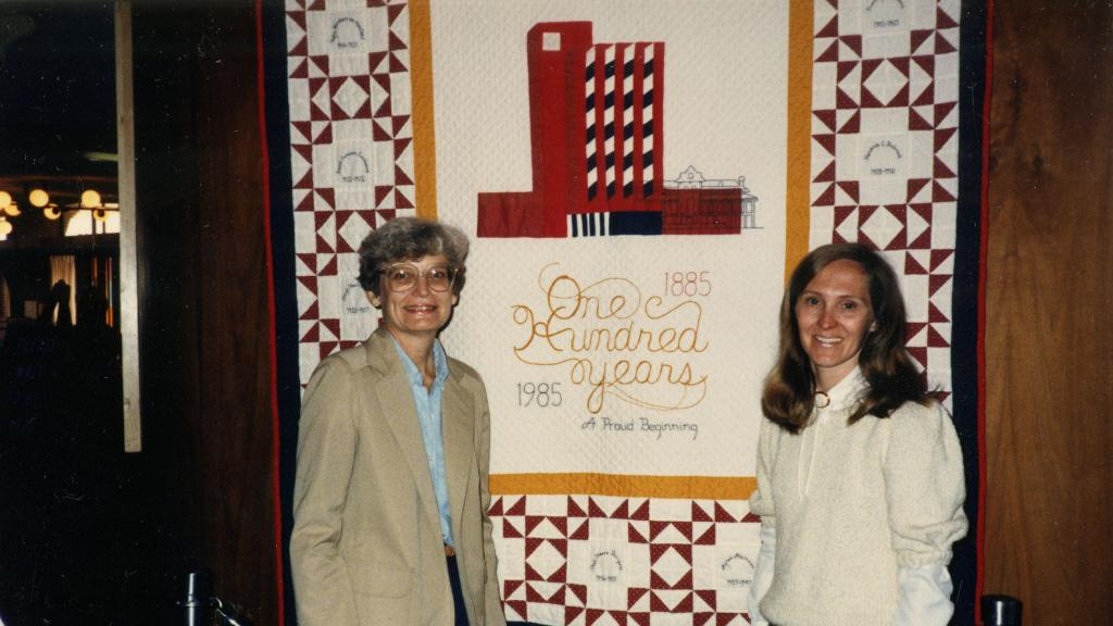 Jan Harelson and Betsy Sales in Front of One Hundred Years Quilt, 1985