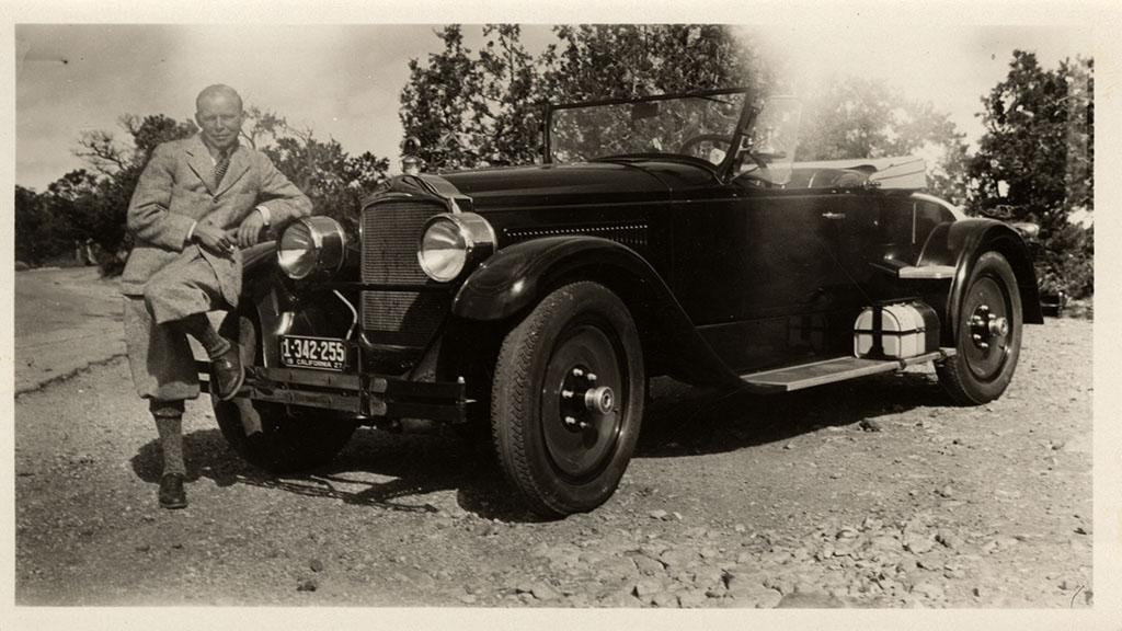 Photograph of Walt Coburn Leaning on a Packard Roadster, 1927