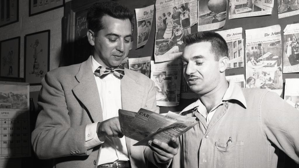 Portrait of Levitz wearing jacket and bow tie looking at materials in his hands alongside another man.