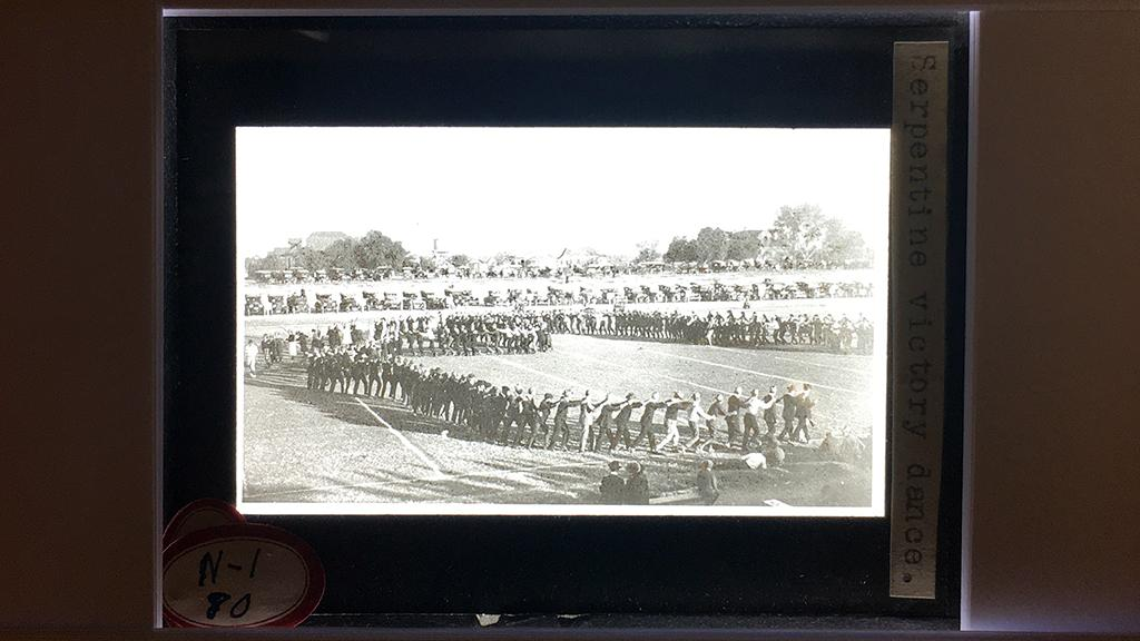 Lantern slide with photograph of parade ground with serpentine victory dance