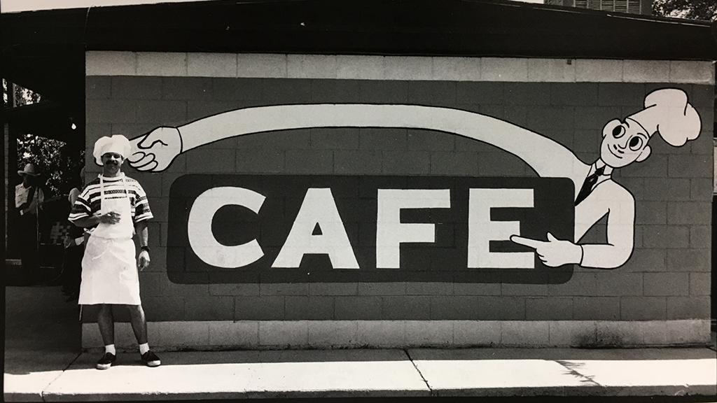 Man in chef hat in front of cafe sign on side of building in Oatman, Arizona