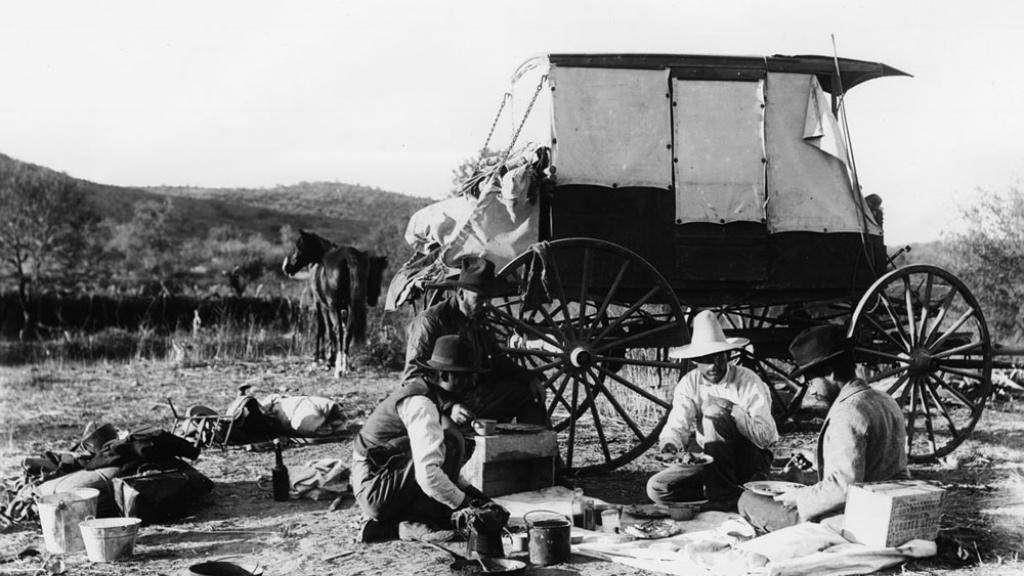 4 men eating a meal. A wagon and their horses are in the background.