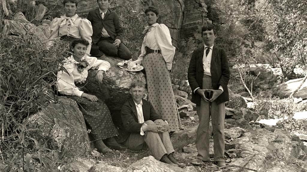 Photograph of six University of Arizona students posing on a rock probably at Sabino Canyon, 1898