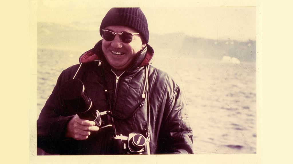 Ray Vicker smiling in front of a body of water in Greenland holding two cameras.
