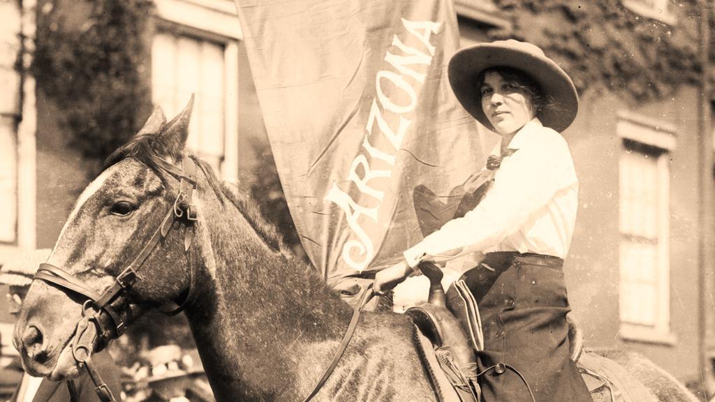 Woman on horse holding a flag