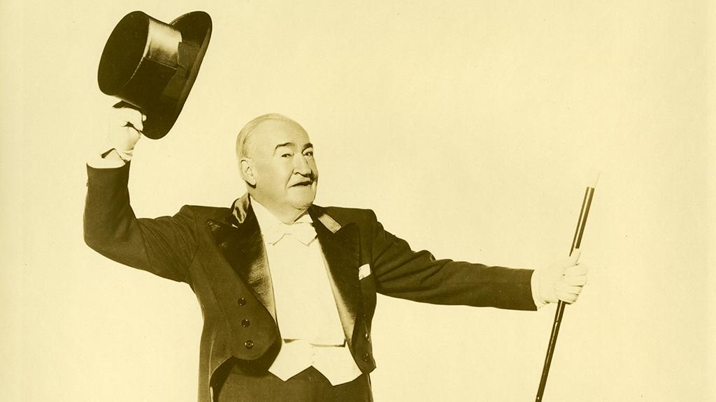 Joseph E. Howard in suit with tails holding top hat and cane.