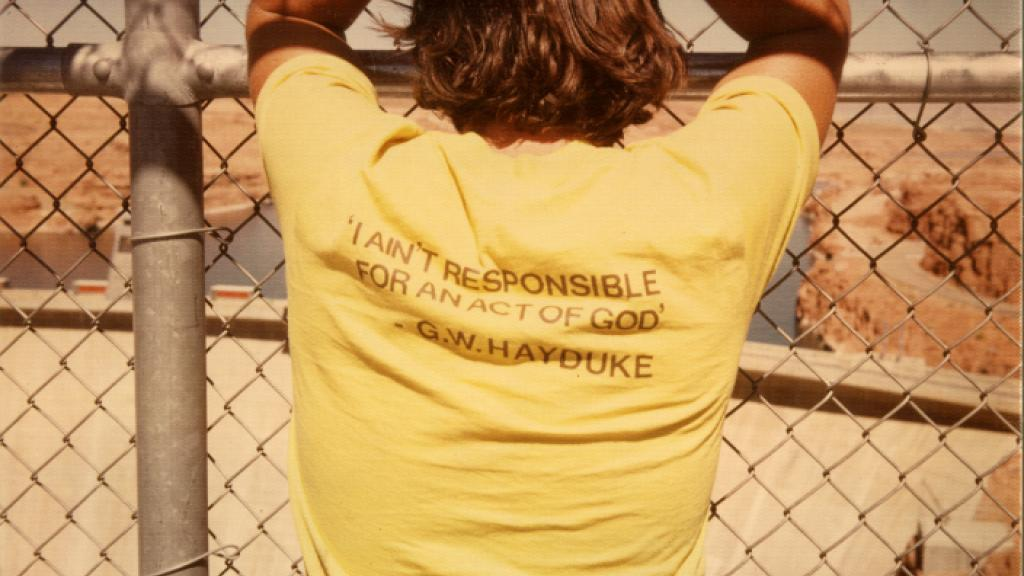 Man Standing in Front of Glenn Canyon Dam Wearing a Shirt with a G.W. Hayduke Quote, undated